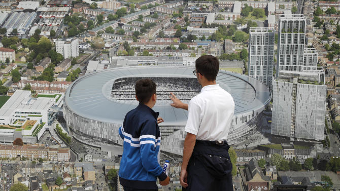 Fans look at plans for the new stadium before the match