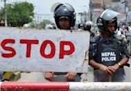 Nepalese police officials stand guard outside the Constitutional Assembly building in Kathmandu. The leader of Nepal's Maoists has called for rival parties to join a national unity government to take the country to fresh elections and said he was open to a change of prime minister