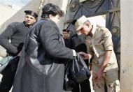 An Egyptian Army soldier inspects a voter's handbag outside a polling station during a referendum on the new constitution in Cairo, January 15, 2014. REUTERS/Mohamed Abd El Ghany