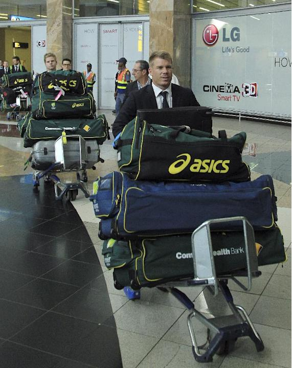 Australia's cricket player David Warner, front, with teammates pushes trolleys with their bags during their arrival at OR Tambo International Airport in Johannesburg, South Africa, Wednesday, Jan.
