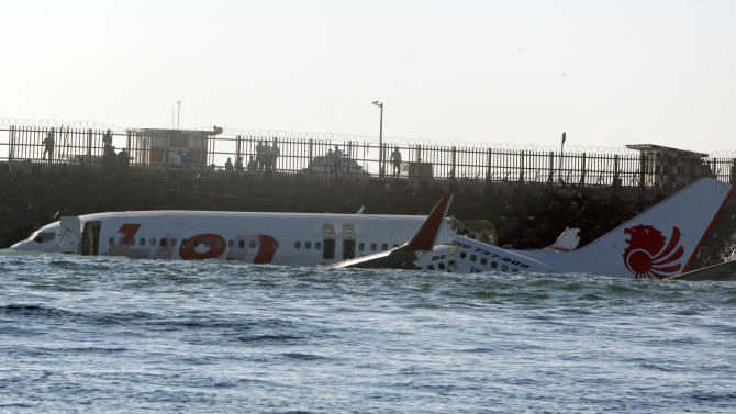 The wreckage of a Lion Air jet sits in the ocean near the airport in Bali, Indonesia on Sunday, April 14, 2013. All 108 passengers and crew survived after the new Lion Air jet crashed into the ocean and snapped into two while attempting to land Saturday on the Indonesian resort island of Bali, injuring up to 45 people. (AP Photo/Firdia Lisnawati)