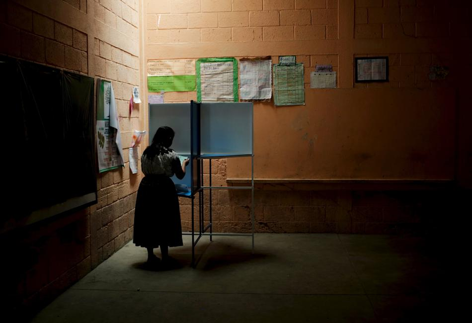 A woman marks her ballot at a polling station during general elections in Guatemala City,