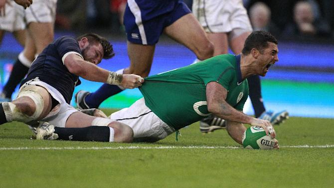 Ireland's Rob Kearney, right, celebrates after scoring a try despite being tackled by Scotland's Ryan Wilson during their Six Nations Rugby Union international match at the Aviva Stadium, Dublin, Ireland, Sunday, Feb. 2, 2014. (AP Photo/Peter Morrison)