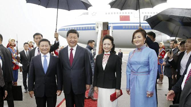 In this photo released by China's Xinhua news agency, Chinese President Xi Jinping, center left, and his wife Peng Liyuan, center right, pose for a photo with Mongolian Prime Minister Norov Altankhuyag and his wife Khonichin Selenge at Ulan Bator airport, Mongolia, Thursday, Aug. 21, 2014. Landlocked Mongolia is hoping to secure better access to Chinese ports as Xi became the first Chinese head of state in more than a decade to visit this sprawling nation sandwiched between China and Russia. (AP Photo/Xinhua, Ju Peng) NO SALES