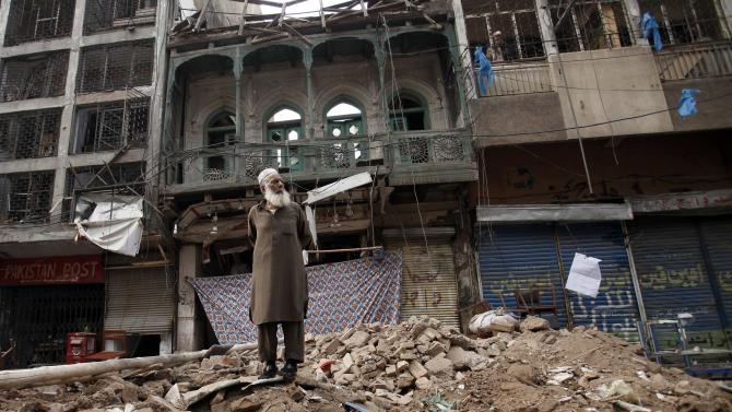 A man stands on a pile of rubble in front of a damaged building after it was hit by a bomb blast, which happened on Sunday, in Peshawar