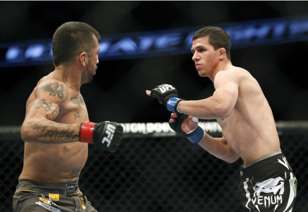 Estevan Payan, left, and Alex White fight in a mixed martial arts event on Saturday, April 19, 2014, at UFC Fight Night in Orlando Fla.. White won. (AP Photo/Reinhold Matay)
