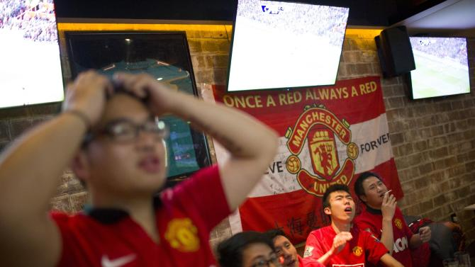 Fans of Manchester United Shanghai fan club react as they watch a telecast of the team's English Premier League soccer match in Shanghai