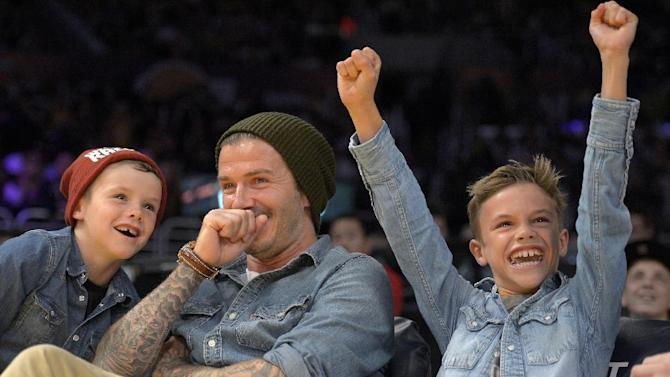 FILE- English Soccer player David Beckham, center, laughs with his sons Romeo, right, and Cruz, left,  as they watch an NBA basketball game between the Los Angeles Lakers and Phoenix Suns, in this file photo dated Friday, Nov. 16, 2012, in Los Angeles, USA.  It is announced Tuesday Dec. 18, 2012 that the son of soccer star David Beckham and former Spice Girl singer Victoria Beckham, ten-year old Romeo Beckham, is the new face of the London based clothing brand Burberry and features in upcoming ads for Burberry's spring/summer 2013 collection. (AP Photo/Mark J. Terrill, file)