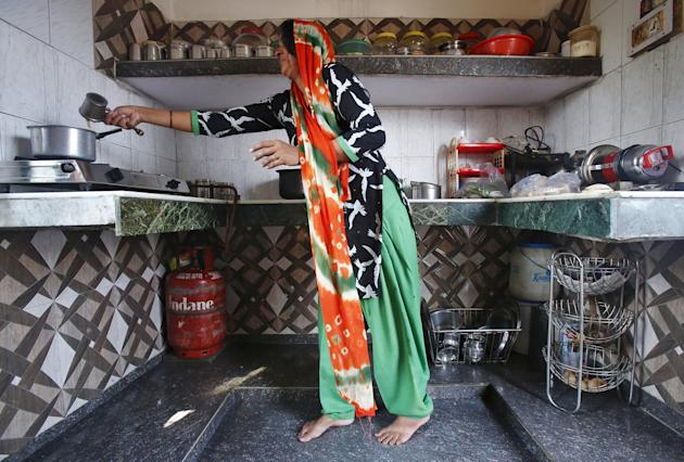 A housewife makes tea on a stove using a Liquefied Petroleum Gas cylinder in her kitchen at Dujana village