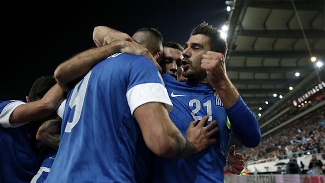 Greece's Kostas Katsouranis, right, celebrates his goal with teammates during their World Cup qualifying playoff first leg soccer match against Romania at the Karaiskaki stadium in the port of Piraeus, near Athens, Friday, Nov. 15, 2013