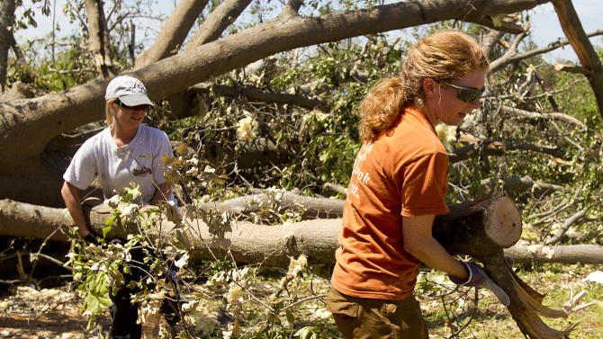 Mary Clair Thompson, right, and Tracy Fessler, along with a group of Auburn students, assist in the clean up of debris on Thursday, May 5, 2011 in Pleasant Grove, Ala. A tornado left a path of total devastation as it passed through on April 27, 2011. (AP Photo/Butch Dill)