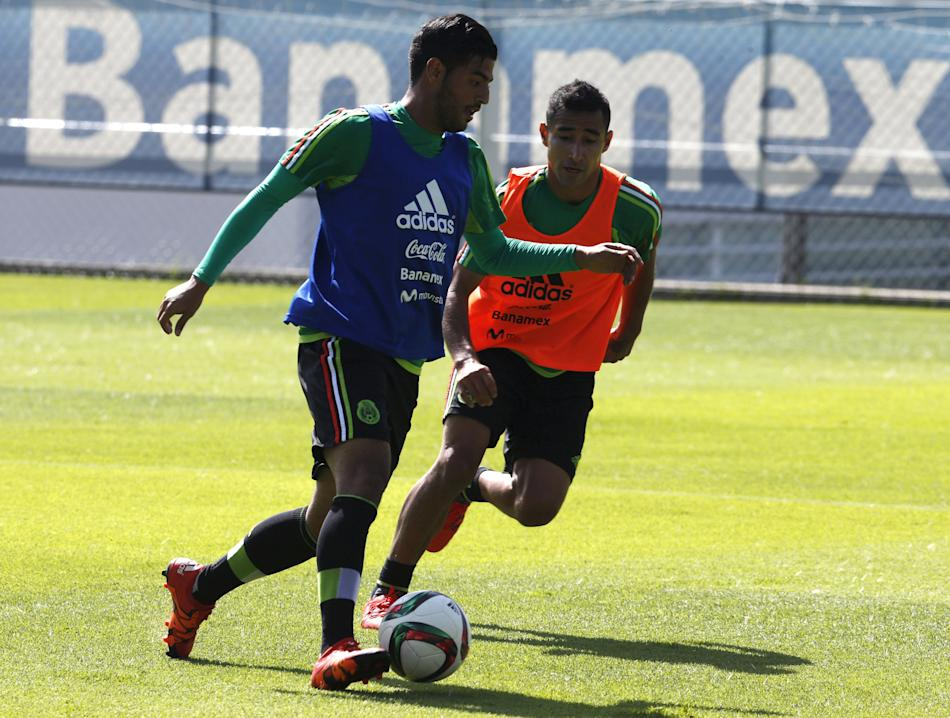 Mexico's striker Carlos Vela controls the ball past teammate during a practice session in Mexico City