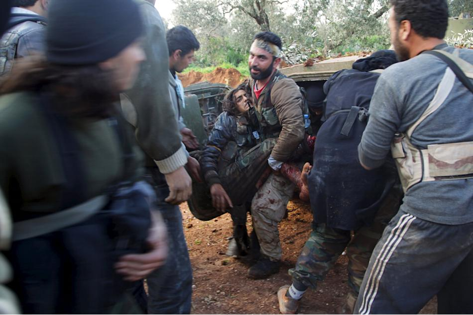 Rebel fighters from the Ahrar al-Sham Islamic Movement help an injured fellow fighter during what they said was an offensive to take the northwestern city of Idlib