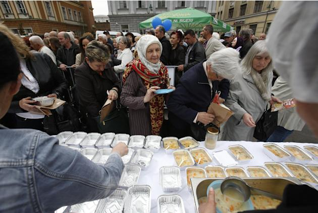Bosnian people gather to taste chicken stew after cooks and volunteers prepared the stew in Sarajevo, on Friday April 17, 2015. Bosnian chefs hope they have broken a Guinness record for the biggest ch