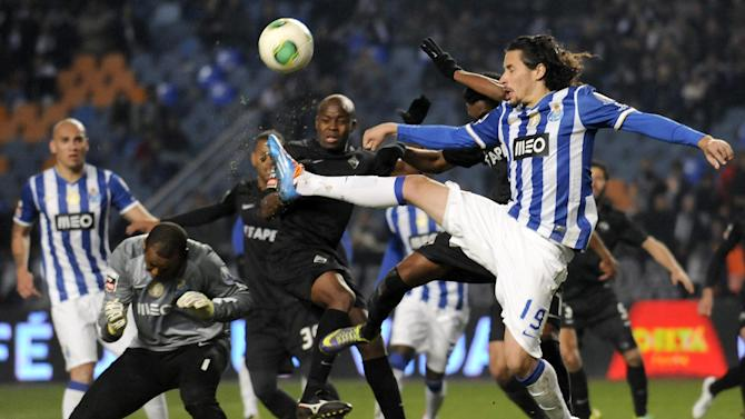 """FC Porto's goalkeeper Helton Arruda, second left, from Brazil, and Luis """"Lica"""" Carneiro, right, go for the ball in the last seconds of a Portuguese League soccer match against Academica at the Municipal Stadium in Coimbra, Portugal, Saturday, Nov. 30, 2013. Academica won 1-0 causing Porto's first defeat in the championship"""