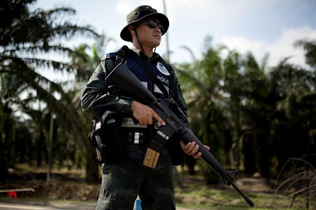 An armed Malaysian policeman mans a security checkpoint in Lahad Datu on March 6, 2013. Malaysian police shot dead a teenager and injured a man Sunday as they tried to end a month-long incursion by Filipino gunmen in remote Sabah state that has seen 62 people killed