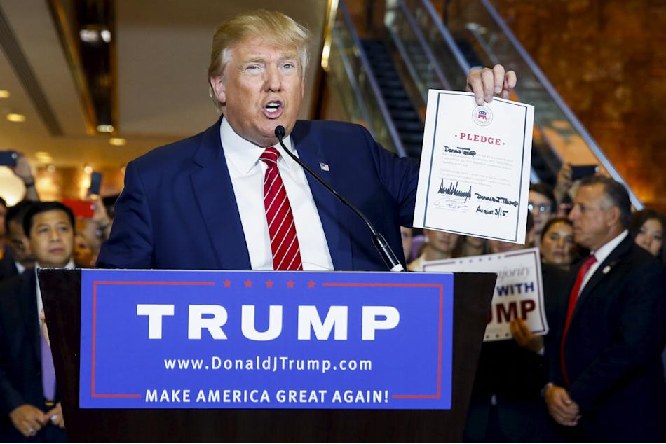 U.S. presidential hopeful Donald Trump holds up a signed pledge during a press availability at Trump Tower in New York