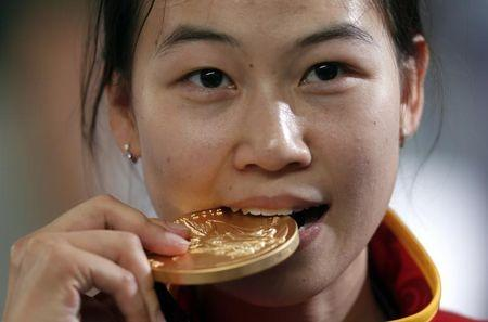 China's Yi Siling bites her gold medal at the victory ceremony after the women's 10m air rifle final competition at the London 2012 Olympic Games in the Royal Artillery Barracks at Woolwich in