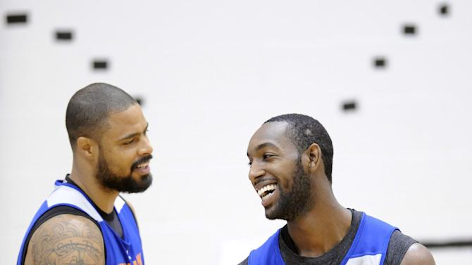 New York Knicks' C.J. Leslie (25) laughs after competing in a shooting drill with Tyson Chandler during NBA basketball training camp Tuesday, Oct. 1, 2013, in Greenburgh, N.Y