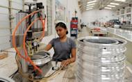 A labourer is seen working at the aluminium wheel laying section of the OREVA E Bike manufacturing facility near Samakhiali of Kutch district, on May 24. Indian economy expanded by a much slower-than-expected 5.3 percent in the January-March quarter, official data showed, adding further pressure on the embattled government