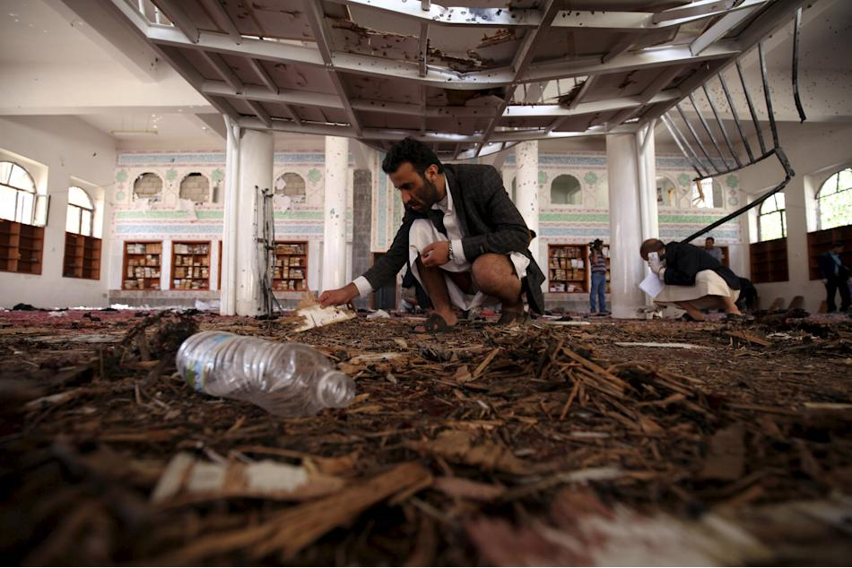 Crime scene investigators look at the ground after a suicide bomb attack at a mosque in Sanaa