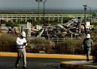 PEMEX workers walk by the place where a fire in the gas plant killed at least twenty-six people in Reynosa, Mexico. The death toll from the fire rose to 29 while three workers remained missing Wednesday as witnesses recounted the terrifying blast and the inferno's intense heat.