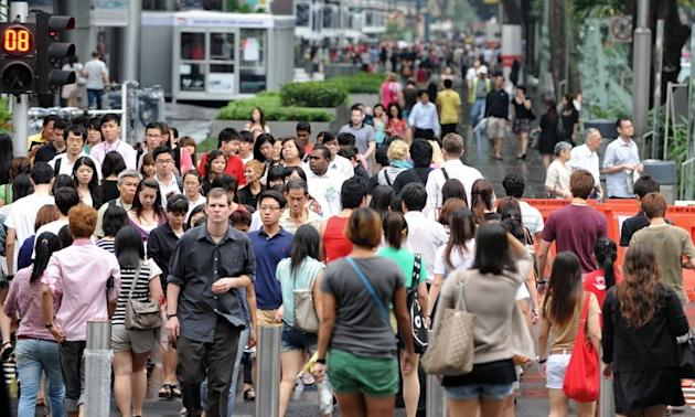 "This file photo shows pedestrians walking along Orchard Road in Singapore's upmarket shopping district, on September 20, 2011. Afghans and Iraqis have been traumatised by years of war but the people of super-rich Singapore are even more miserable, coming dead last in a Gallup ranking of ""positive emotions"" around the world"