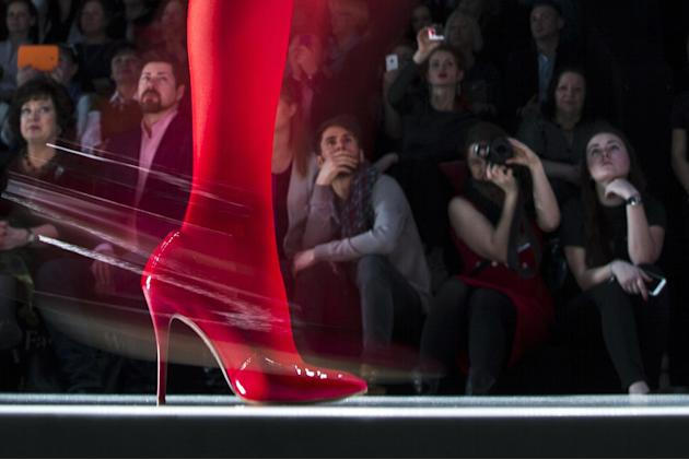 FILE - In this file photo dated  Friday, March 27, 2015, spectators watch as a model displays a creation by Russian designer Slava Zaitsev during Fashion Week, in Moscow, Russia. (AP Photo/Pavel Golov