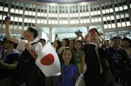 "A girl waves Japan's national flag as visitors take photos during an event titled ""Tokyo 2020 Host City Welcoming Ceremony"", upon the delegation's return, at the Tokyo Metropolitan Government Building in Tokyo September 10, 2013. REUTERS/Issei Kato"