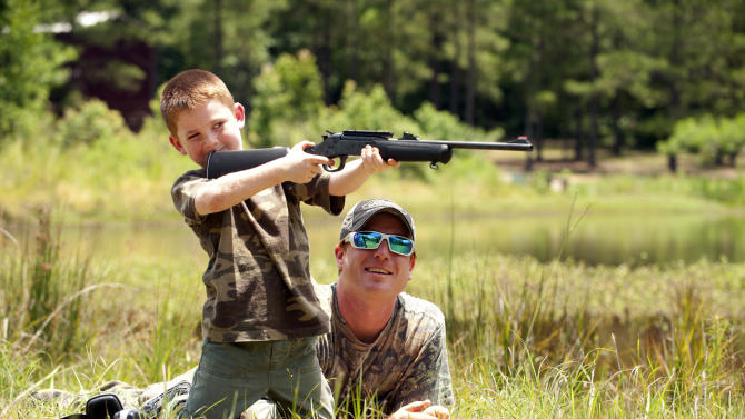 Chavez helps his son with target practice before a wild hog hunt at Great Southern Outdoors Wildlife Plantation in Union Springs