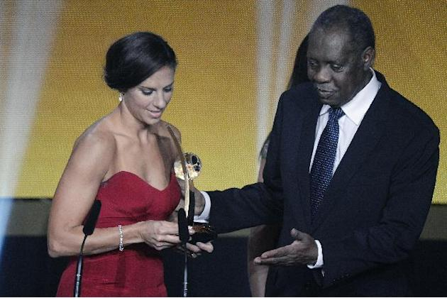 Carli Lloyd of the USA delivers a speech next to acting FIFA President Issa Hayatou after winning the FIFA Women's soccer player of the year 2015 prize during the FIFA Ballon d'Or awarding cer