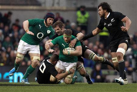 Ireland's Heaslip is challenged by New Zealand's Cruden and McCaw in International rugby union match in Dublin