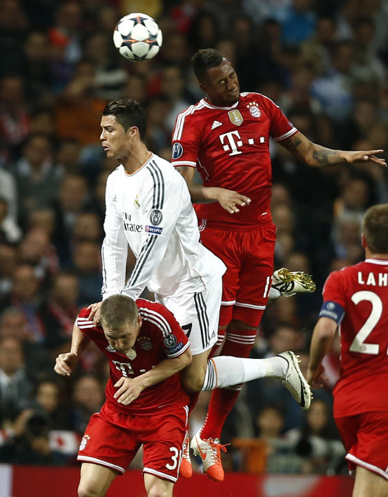 Real's Cristiano Ronaldo and Bayern's Jerome Boateng go for a header next to Bayern's Bastian Schweinsteiger, during a first leg semifinal Champions League soccer match between Real Madrid