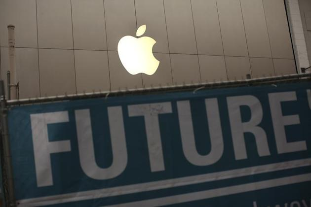 The Apple logo is pictured on the front of the company's flagship retail store near signs for the central subway project in San Francisco, California January 23, 2013. REUTERS/Robert Galbraith