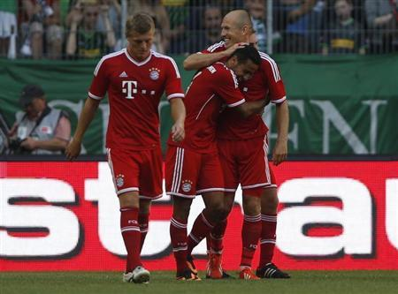 Bayern Munich's Thiago of Spain celebrates his goal against Borussia Moenchengladbach with Robben and Kroos during their Telekom Cup soccer match in Moenchengladbach