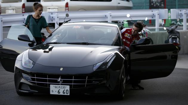 Ferrari Formula One driver Alonso of Spain and his girlfriend Kapustina leave after qualifying session of the Japanese F1 Grand Prix at the Suzuka circuit