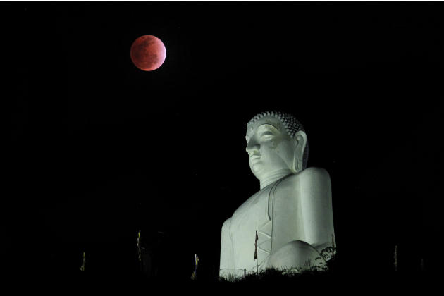 A lunar eclipse is seen in the sky beside a statue of Buddha in Kurunegala, Sri Lanka, Saturday, Dec. 10, 2011. (AP Photo/ Eranga Jayawardena)