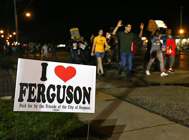 A small group of protesters marches down West Florissant Avenue in Ferguson, Mo. on Wednesday.