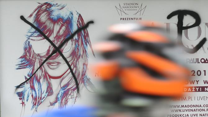 A cyclist rides past a defaced Madonna concert billboard in Warsaw, Poland, Wednesday, July 18, 2012.  Organizers of the concert have agreed to a request from city officials to start the show with a minute of silence and a brief clip about the 1944 revolt against Nazi rule, the Warsaw Uprising, in a nod to war veterans. Some veterans and young Catholics have voiced anger that the Aug. 1 concert falls on the 68th anniversary of the uprising, a day marked with a somber tone. The sign on the right of the billboard is the symbol of Poland's fight against the Nazis. The sign on the right of the billboard is the symbol of Poland's fight against the Nazis. (AP Photo/Alik Keplicz)