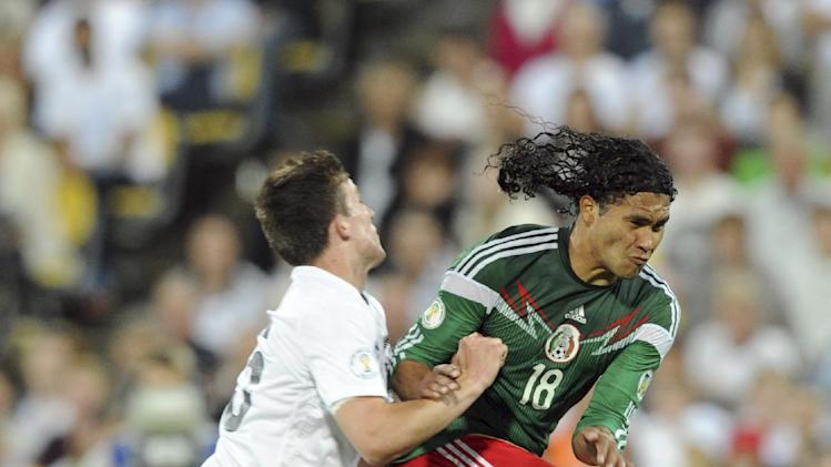 New Zealand's Michael McGlinchey, left, clashes with Mexico's Carlos Pena during their World Cup qualifying soccer match at Westpac Stadium, in Wellington, New Zealand, Wednesday, Nov. 20, 2013. Mexico qualified for the World Cup after beating New Zealand 4-2 in the second leg of an inter-continental playoff Wednesday, bringing an end to one of its most troubled and divisive qualifying campaigns