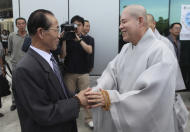 Sim Sang Jin from North Korea's Buddhist Association, left, shakes hands with Ri Kyong-sik of South Korea's Jogye Buddhist sect at Pyongyang airport in Pyongyang, North Korea, Saturday, Sept. 3, 2011. Due to political tensions, South Korean citizens are prohibited from traveling to North Korea without government permission. However, the religious delegation received approval in Seoul to make the rare trip to attend a ceremony at ancient Pohyon Temple in the mountains northwest of the North Korean capital. (AP Photos/APTN)