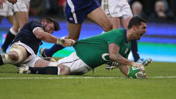 Ireland's Rob Kearney, right, celebrates after scoring a try despite being tackled by Scotland's Ryan Wilson during their Six Nations Rugby Union international match at the Aviva Stadium, Dublin, Ireland, Sunday, Feb. 2, 2014
