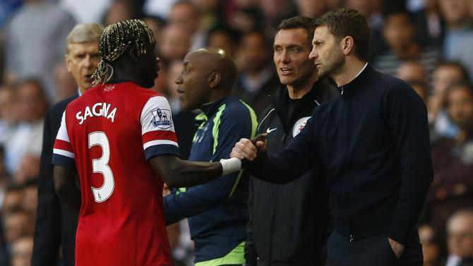 Tottenham Hotspur's manager Sherwood shakes hands with Arsenal's Sagna after throwing the ball at him during their English Premier League soccer match in London
