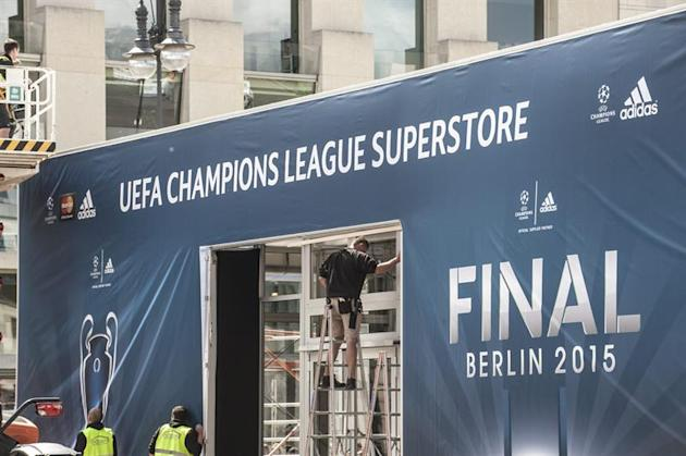 BER009. Berlin (Germany), 30/05/2015.- A worker stands on a ladder in front of a tent that reads 'UEFA Champions League Superstore' in Berlin, Germany, 30 May 2015. FC Barcelona will face Juve