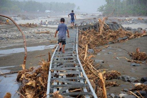 Boys play on a destroyed bridge at Kapay river, in Iligan City, southern Philippines, today
