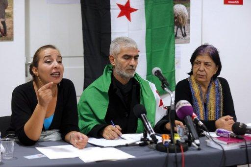 Kamal Jamal Beck (C), former director of programming at the official SANA radio and the SANA online news website in Damascus, listens during a press conference in Paris, on December 28, 2012, as he and two other colleagues from the radio service, Lama Al-Khadra (L) and Baddour Abdel Karim (R), announce their recent defection from official Syrian state media