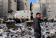 Syrian people are pictured in a bazaar next to a garbage heap in the northern city of Aleppo, on February 14, 2013. Syria's rebels captured a military airbase in the northern province of Aleppo and geared for a major battle against loyalist forces for control of two nearby strategic airports