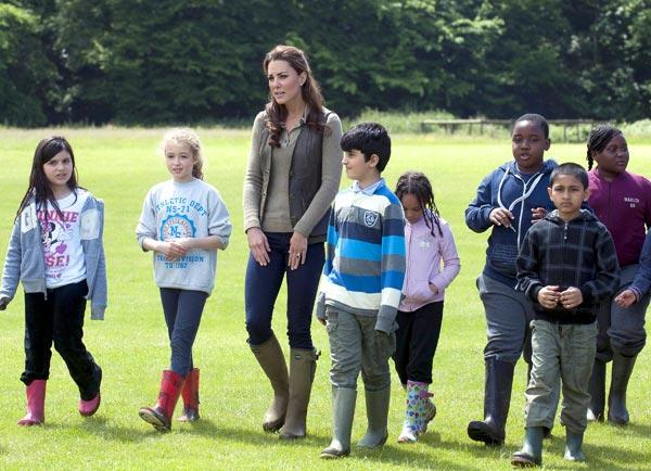 Kate hangs out with young children during a visit to the 'Expanding Horizons' Primary School Project in England. She knows how to keep it casual but still flattering in dark jeans, wellies, a fitted t