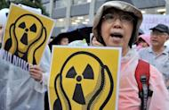 """People shout slogans during a demonstration denouncing nuclear power plants, on July 20. Thousands of people are expected to form a """"human chain"""" around Japan's parliament on Sunday as part of demonstrations aimed at ending nuclear power after last year's atomic crisis at Fukushima"""