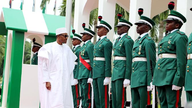 Nigerian president Mohammadu Buhari (L) inspects guards of honour as part of Nigeria's independence anniversary celebrations on October 1, 2015 in Abuja